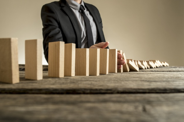 https://podoleanu-paun.ro/wp-content/uploads/2021/04/businessman-wearing-suit-standing-beside-series-vertical-wooden-slabs-as-they-fall-one-after-another-concept-domino-effect-where-one-business-failure-causes-further-collapses_254268-1063.jpg